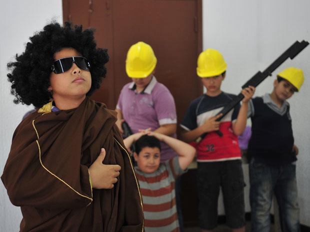 Crianças atuaram em uma peça teatral com cenas mostrando as forças do ditador líbio Muammar Kadhafi prendendo rebeldes. A peça foi montada em Benghazi, cidade dominada por rebeldes que exigem a saída de Kadhafi do governo. Um garoto usou uma peruca e óculos escuros para atuar no papel do ditador. (Foto: Reuters)
