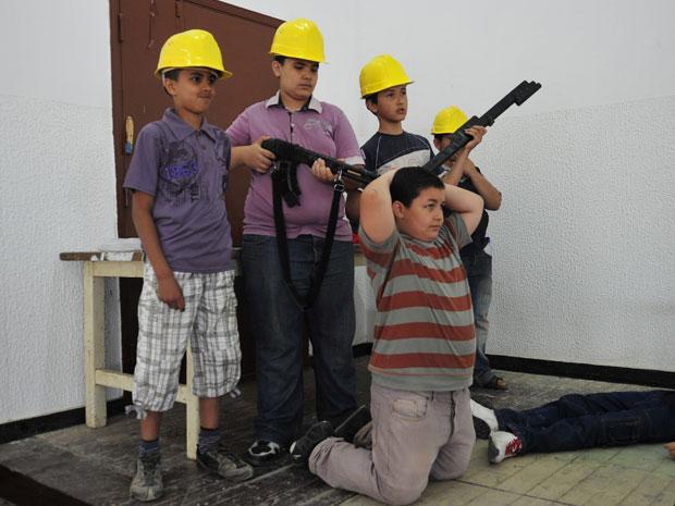 Os meninos com capacetes amarelos representavam as forças leais a Muammar Kadhafi. Os outros atuaram nos papéis de rebeldes capturados pelos soldados do governo. No final da peça, todos fizeram um apelo por paz. (Foto: Reuters)