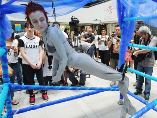 Artista britânica Alice Newstead atrai curiosos ao ficar pendurada por ganchos em protesto contra o abate ilegal de tubarões em Hong Kong, nesta terça-feira (14). (Foto: Mike Clarke / AFP)