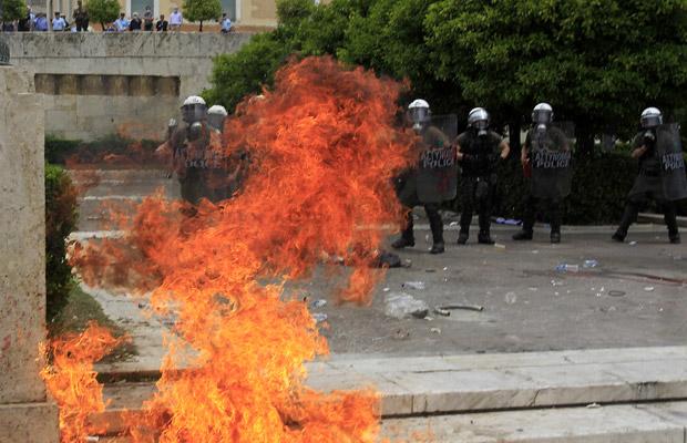 Manifestantes lançam bomba de gasolina em policiais nesta quarta-feira (15) na Praça Syntagma, em Atenas (Foto: AP)