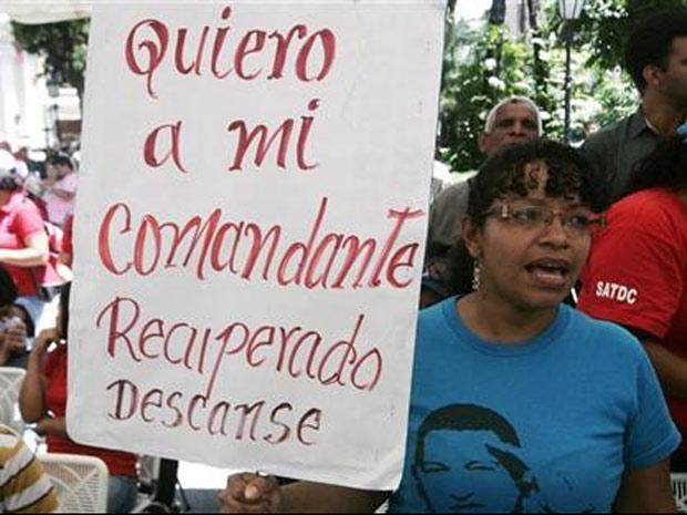 """Mulher exibe cartaz de apoio ao presidente venezuelano, Hugo Chávez, com os dizeres: """"Quero meu comandante recuperado, descanse"""", em Caracas, na Venezuela (Foto: dwin Montilva / Reuters)"""