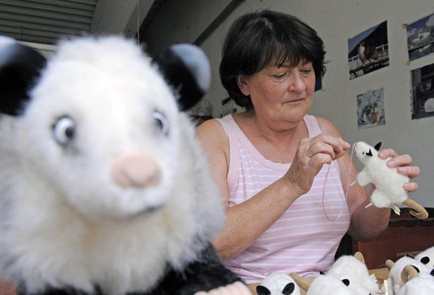 A funcionária Helga Myrau costura o nariz de um dos bichos de pelúcia na fábrica no leste da Alemanha (Foto: AP)