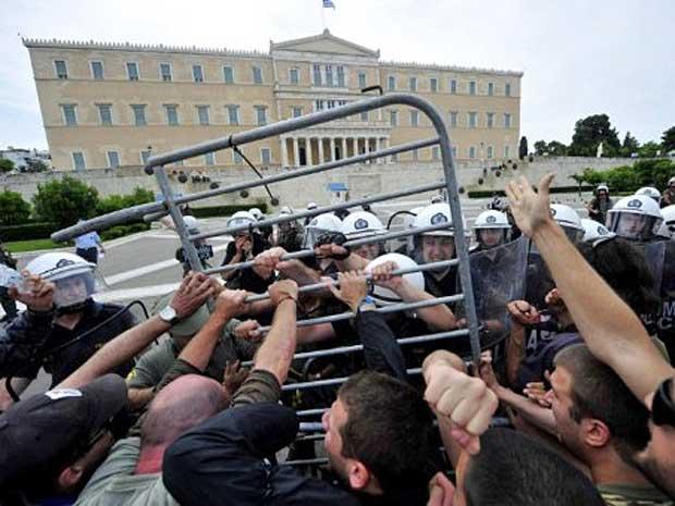 Policiais e manifestantes entram em confronto em frente ao Parlamento grego, durante greve geral contra planos de austeridade do governo, em Atenas. (Foto: Aris Messinis / AFP Photo)