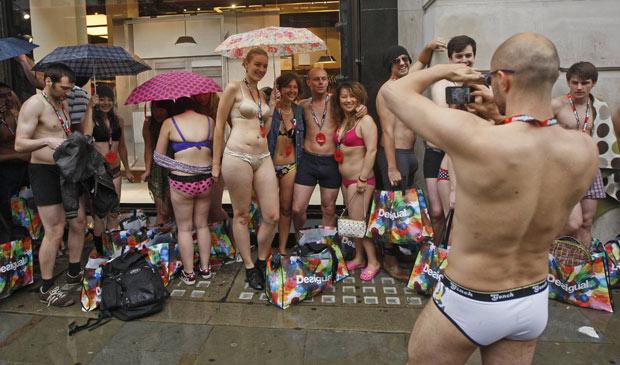 Vestidos apenas com roupas de baixo, compradores se protegem da chuva enquanto esperam abertura de loja em Londres; a loja de moda Desigual iniciou nesta quinta uma liquidação e ofereceu aos primeiros 100 clientes que comparecessem em roupas íntimas duas peças de graça  (Foto: Luke MacGregor / Reuters)