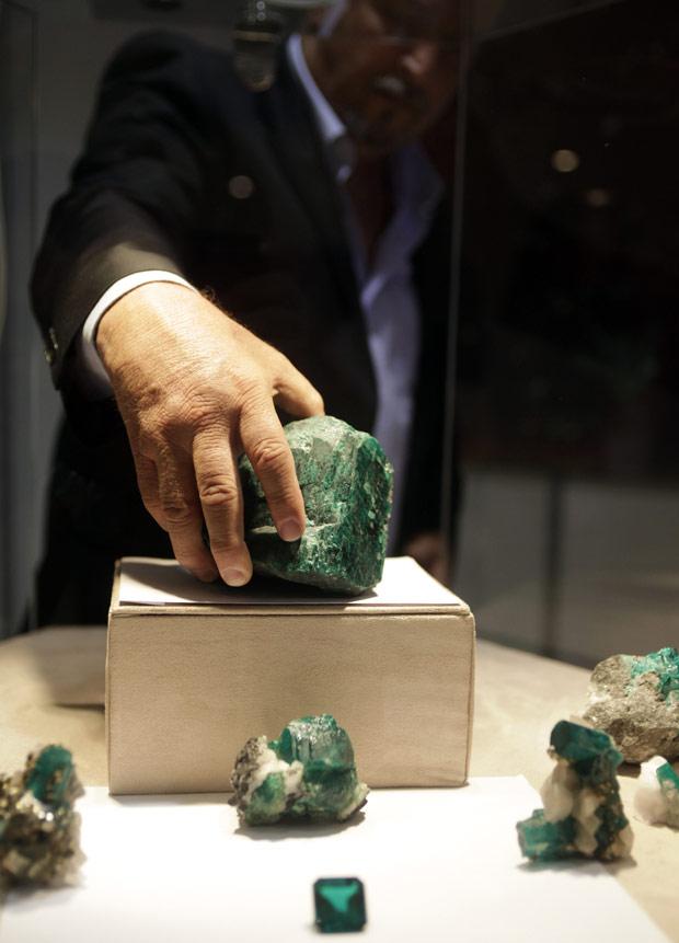 Homem manipula a pedra, uma das maiores esmeraldas já produzidas, que está sendo exibida pela primeira vez na Colômbia  (Foto: Fernando Vergara / AP)