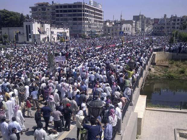Centenas de manifestantes pedem a saída do presidente Bashar al-Assad na cidade síria de Deir al-Zour, próxima à fronteira com o Iraque (Foto: Reuters)