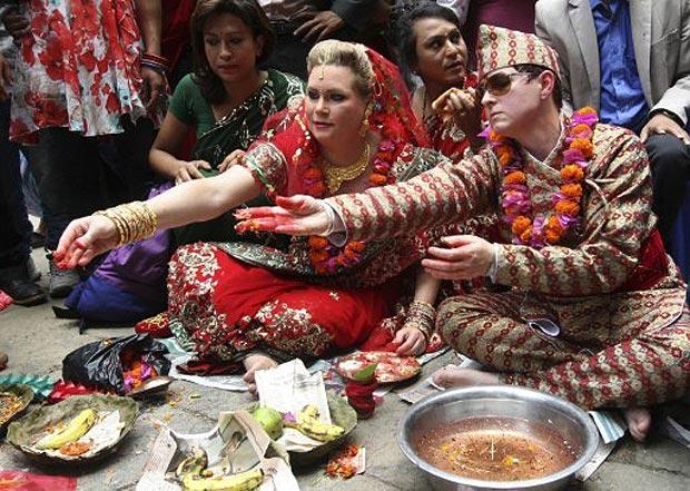 Sarah Welton, à esquerda, e Courtney Mitchell, à direita, realizam rituais em cerimônia de casamento em um templo hindu (Foto: AFP)