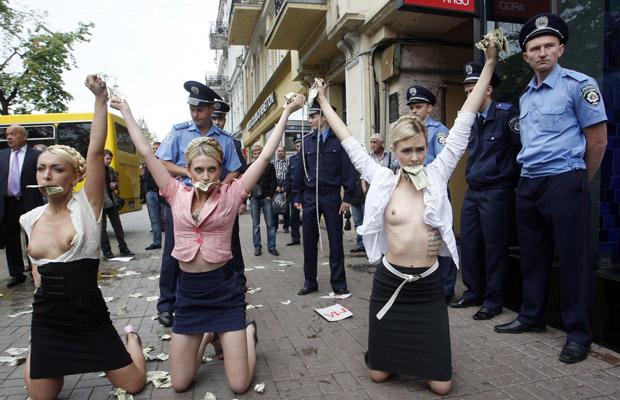 Ativistas do Femen imitam a líder oposicionista Yulia Tymoshenko nesta segunda-feira (20) em frente ao tribunal onde o ex-ministro do Interior da Ucrânia Yuri Lutsenko é julgado por abuso de poder. O Femen contesta o papel do partido da ex-primeira-ministra na oposição (Foto: AP)