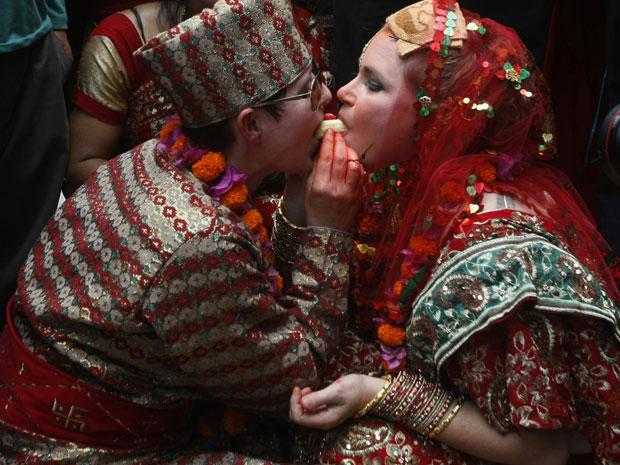 Sarah Welton, à direita, e Courtney Mitchell dividem uma banana em ritual realizado em cerimônia de casamento em um templo hindu (Foto: AP)