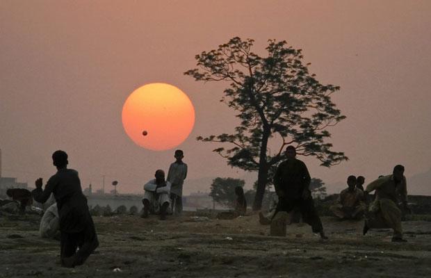 Refugiados afegãos jogam cricket em favela de Islamabad, no Paquistão (Foto: Anjum Naveed/AP)