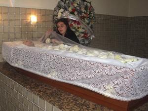 Paola Fenza arruma uma flor no caixão da mãe Wilza Carla (Foto: Lilian Quaino/G1)