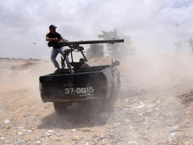 Rebelde lança foguete contra forças de Kadhafi no front de Dafniya, próximo a Misrata, nesta quarta-feira (22) (Foto: AP)