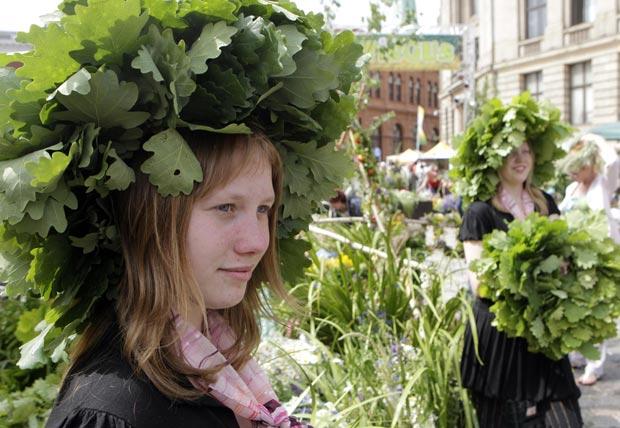 Vendedoras vestem guirlandas feitas com folhas de árvores (Foto: Reuters)