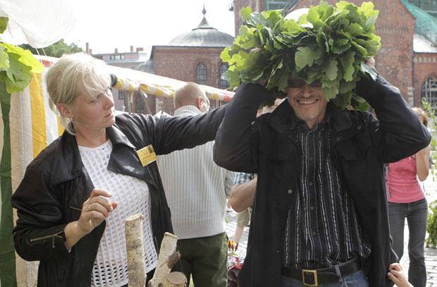 Homem prova grinalda, preparando-se para as comemorações do solstício (Foto: Reuters)