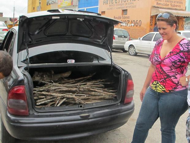 Estudante de mestrado Ana Michele de Almeida compra madeira para acender fogueira na véspera de São João (Foto: Daniel Buarque/G1)
