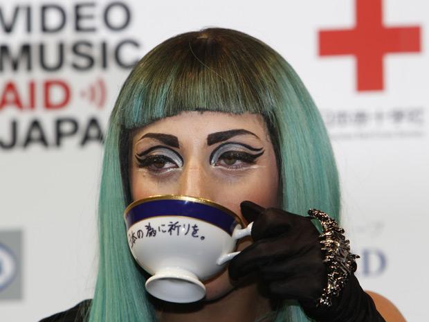 Lady Gaga posa com xícara com mensagem em japonês que pede orações para o Japão, durante entrevista em Tóquio (Foto: Shizuo Kambayashi / AP )