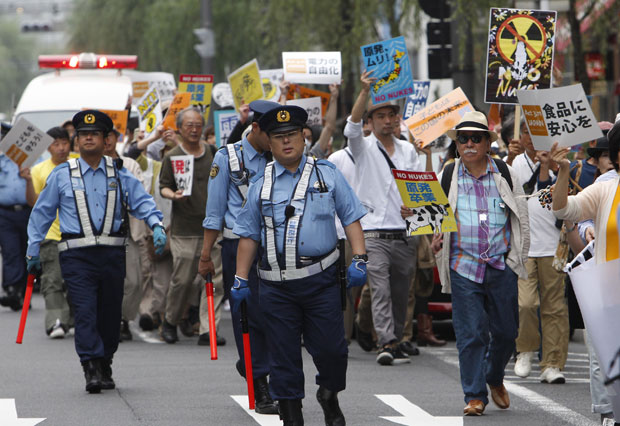 Pessoas fazem protesto em frente à sede da Tokyo Electric Power Co. (Tepco) neste domingo (26) em Tóquio (Foto: AP)