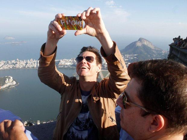Jim Carrey tira fotos durante visita ao Corcovado neste domingo (27).  (Foto: Gabriel Reis e Delson Silva / AgNews)