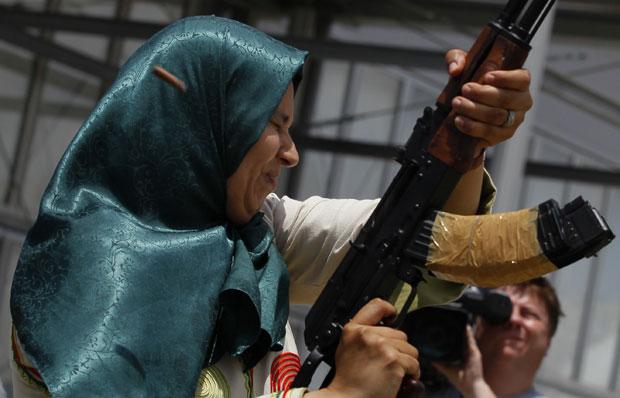 """Mulher líbia fecha os olhos enquanto dispara ao ar durante cerimônia de graduação após curso de manejo de armas em Trípoli neste domingo (26). A foto foi feita em um passeio organizado para a mídia pelo governo. O porta-voz líbio, Moussa Ibrahim, disse que oficiais do país entregaram cerca de 1,2 milhão de armas e está treinando pessoas nos territórios sob o comando de Muammar Kadhafi para impor um """"desafio aos rebeldes"""", que lutam para depor o ditador. (Foto: Ivan Sekretarev/AP)"""
