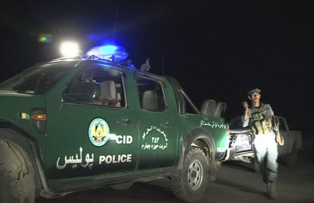 Policial aproxima-se do hotel após o ataque da noite desta terça-feira (28) em Cabul (Foto: AP)
