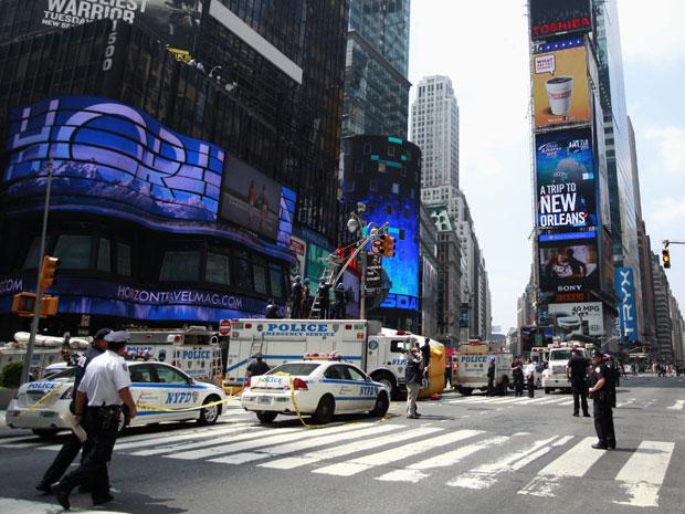 Oficiais do departamento de polícia de Nova York isolaram nesta terça-feira (28) a famosa área do Times Square, em Manhattan, quando um homem não identificado subiu em um poste de luz central e ameaçou se jogar lá de cima. (Foto: Brendan McDermid/Reuters)