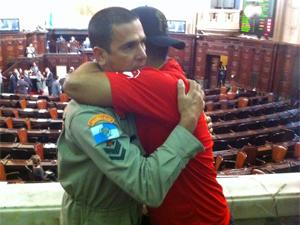 Bombeiros se abraçam após decisão unânime de projeto de lei (Foto: Tássia Thum/G1)
