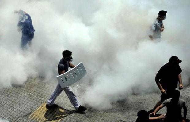 Manifestantes com máscara caminham em meio a gás lacrimogênio jogado pela polícia em protesto em frente ao Parlamento grego (Foto: Filippo Monteforte/AFP)