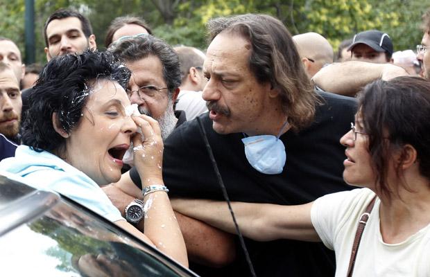 A parlamentar comunista Liana Kanelli limpa o rosto após ter sido atingida por iogurte na chegada ao prédio do Parlamento da Grécia em Atenas nesta quarta-feira (29) (Foto: AP)