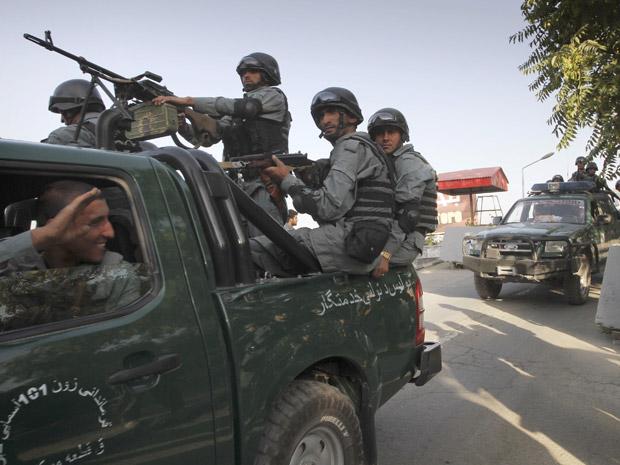 Militares afegãos montam guarda nesta quarta-feira (29) nos fundos do hotel atacado em Cabul (Foto: AP)
