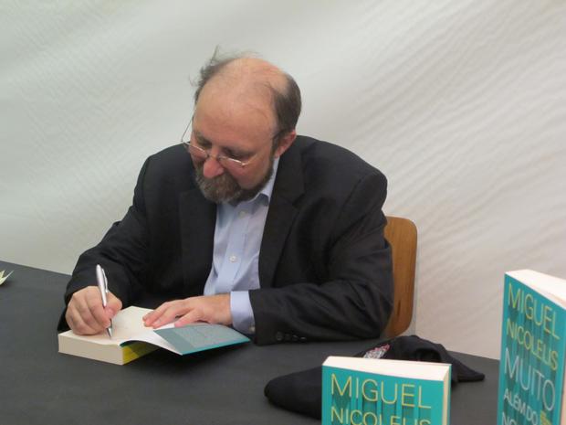 Miguel Nicolelis autografa um exemplar de 'Muito Além do  Nosso Eu' (Foto: Tadeu Meniconi / G1)
