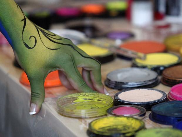 Modelo mostra tintas usadas para criar as pinturas (Foto: Reuters)
