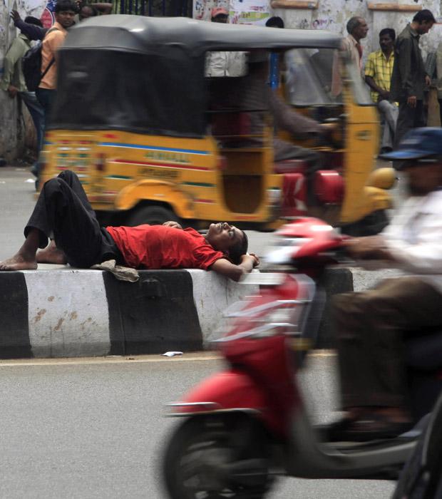 Alheio ao movimento, sem-teto descansa em divisa entre as pistas de uma rua movimentada em Hyderabad, na Índia, neste sábado (2). O flagrante foi feito pelo fotógrafo Mahesh Kumar A. (Foto: AP)