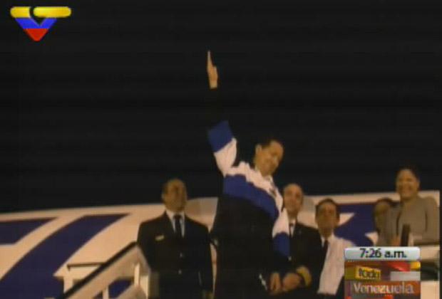 O presidente da Venezuela, Hugo Chávez, acena ao chegar ao país nesta segunda-feira (4) (Foto: Reprodução)