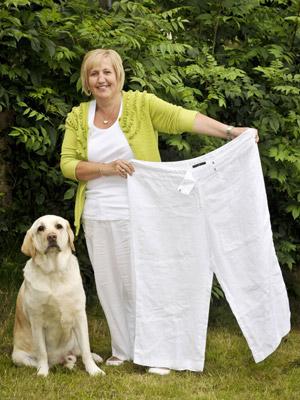Alyson, ao lado de Lucky, mostra calça que usava antes de emagrecer (Foto: BBC)