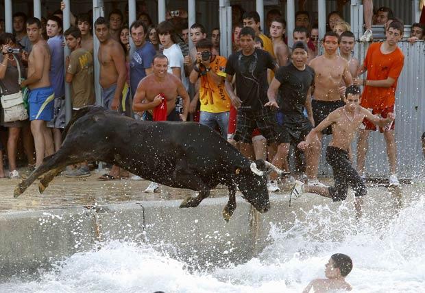 Jovem parece 'caminhar' sobre a água na tentativa de fugir do touro. (Foto: Heino Kalis/Reuters)