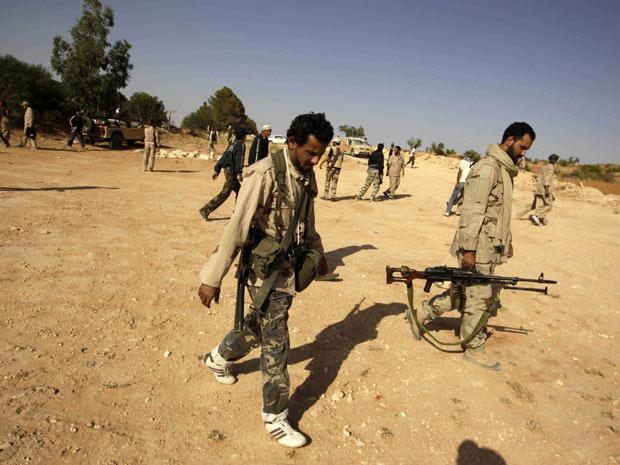 Rebeldes caminham para tomar posição em estrada que leva a Al-Quwalish, povoado perto de Trípoli, nesta quarta (13) (Foto: Ammar Awad / Reuters)