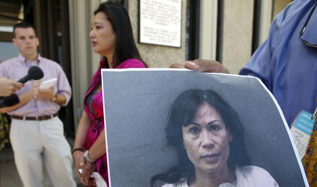 Susan Kang Schroeder (c), relações públicas da Procuradoria de Orange County, fala à imprensa após o depoimento de Catherine Kieu Becker, cuja foto é exibida à direita (Foto: AP)