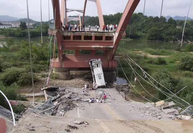 Ônibus de turismo caído após a ponte Wuyishan Gongguan ter se partido em Wuyishan, na província chinesa de Fujian, nesta quinta-feira (14). O acidente matou uma pessoa e feriu 22, durante a manhã, segundo autoridades locais citadas pela agência Xinhua (Foto: AP)