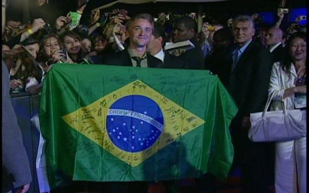 O ator Tom Felton segura bandeira nacional brasileira na chegada ao Morro da Urca (Foto: G1)