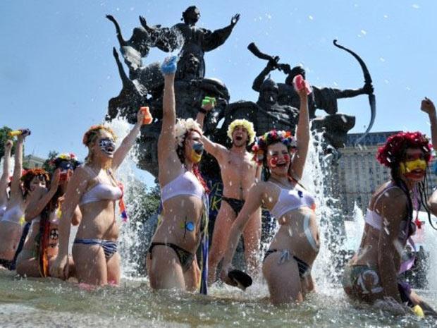 Caracterizados como torcedores de vários países, integrantes do grupo ativista Femen tomam banho em fonte da Praça da Independência, em Kiev, na Ucrânia, nesta quinta (14) (Foto: Sergei Supinsky / AFP)