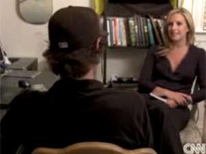 O jornalista americano William Breathes, de costas para não revelar sua identidade real, durante entrevista à rede de TV CNN (Foto: Reprodução)