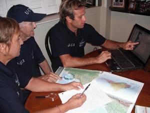 Equipe de pesquisadores analisam dados em computador de veleiro em SC (Foto: Divulgação/Família Schurmann)