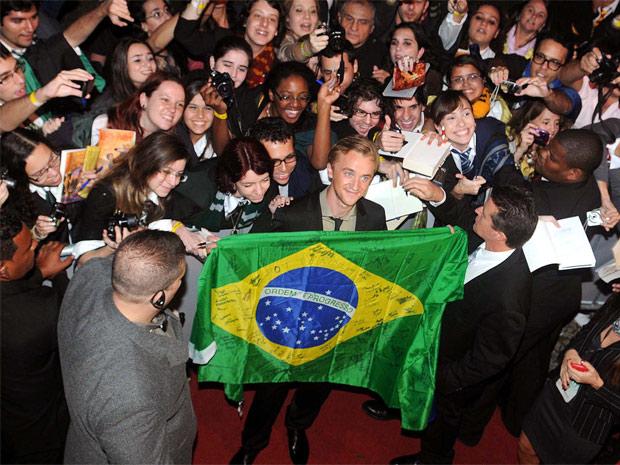 O ator Tom Felton segura bandeira nacional brasileira na chegada ao Morro da Urca (Foto: Alexandre Durão/G1)