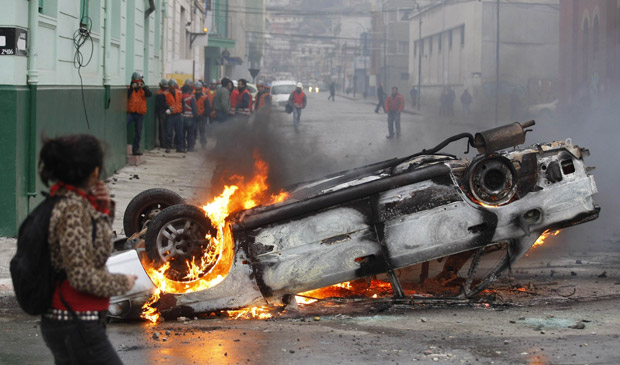 Carro incendiado durante os protestos que deixaram ao menos 40 feridos no Chile, na quinta (14) (Foto: Eliseo Fernandez / Reuters)