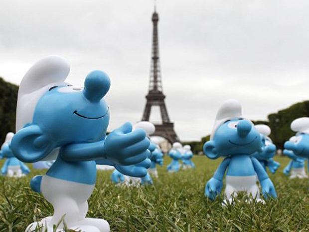 Personagens do Smurfs são expostos em Paris, com a Torre Eiffel ao fundo (Foto: AFP)