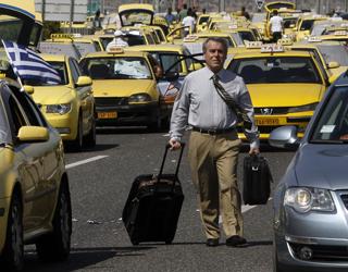 Um passageiro caminha entre os táxis que fazem protesto perto do aeroporto internacional de Athens International airport, (Foto: Reuters)