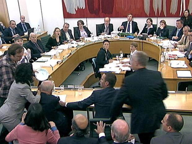 Imagem de vídeo mostra o agressor (à esquerda) indo em direção de Rupert Murdoch (Foto: AP)