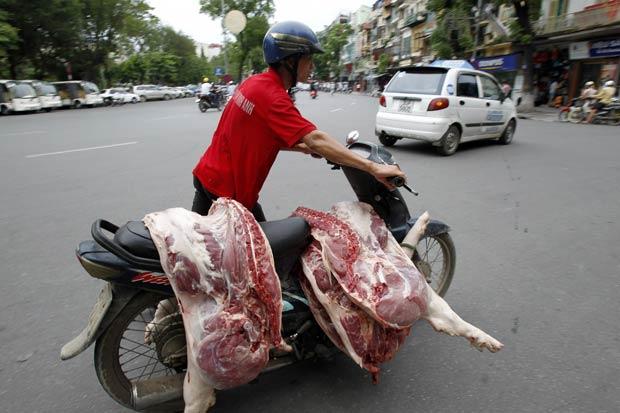 Um homem foi flagrado nesta terça-feira (19) em Hanói, no Vietnã, carregando peças de um porco carneado em uma motoneta. (Foto: Reuters)