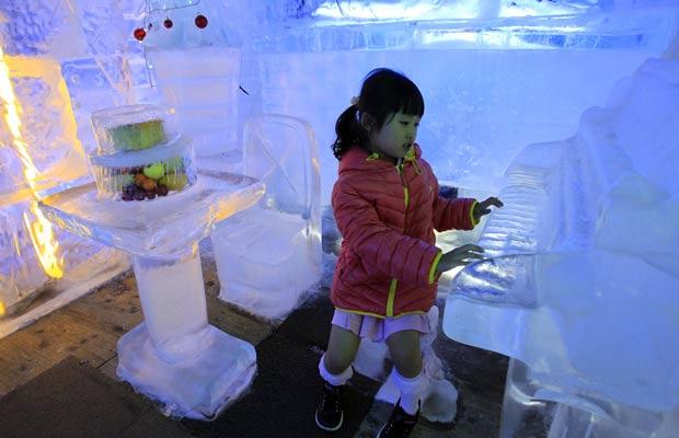 Menina 'toca' piano de gelo, um dos objetos da casa de gelo. (Foto: Lee Jin-man/AP)