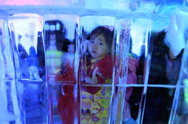 Menina olha através de parede de gelo. (Foto: Lee Jin-man/AP)